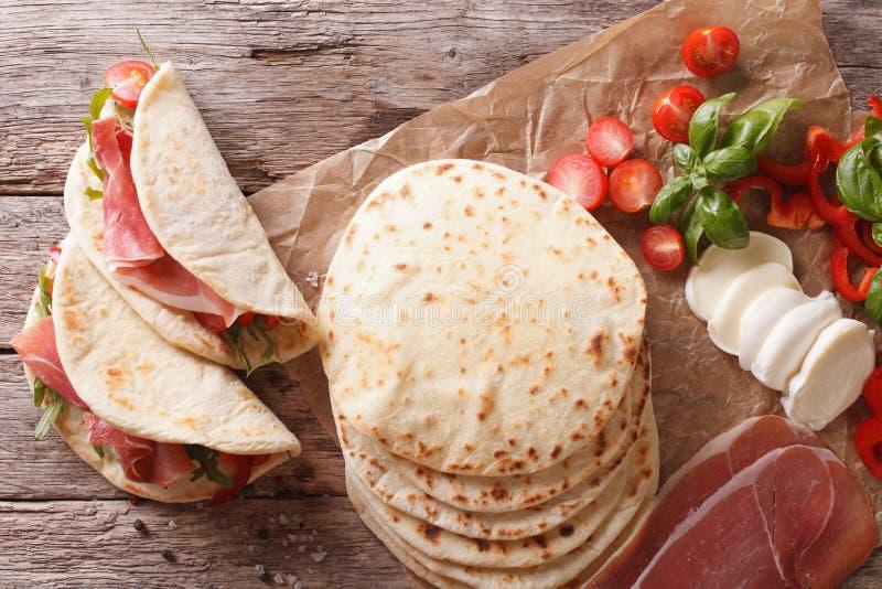 Alimento italiano della via: piadina con i clo del prosciutto, del formaggio e delle verdure immagini stock