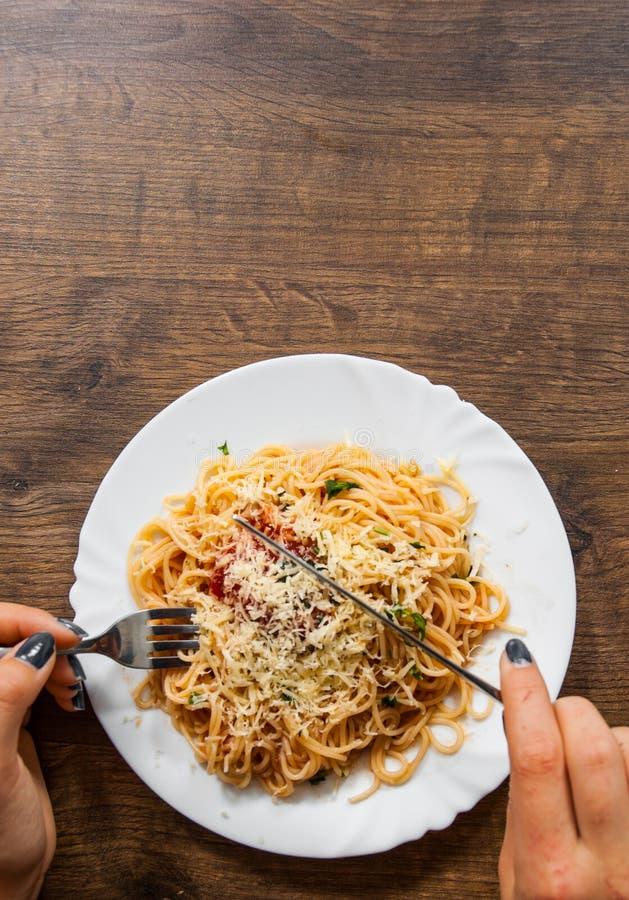 Alimento italiano Mão da mulher que guarda a forquilha com espaguetes bolonhês na placa branca na tabela de madeira Com espaço da fotografia de stock royalty free