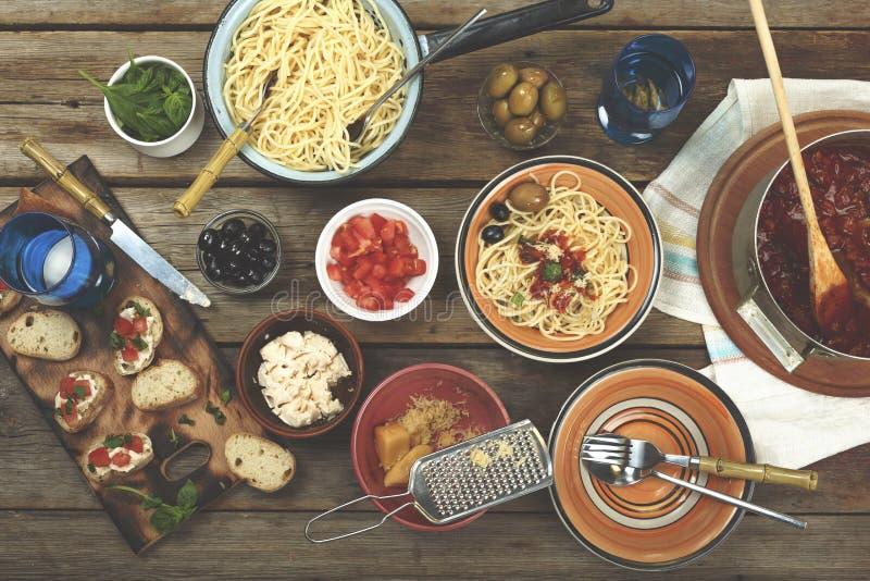 Alimento italiano tradicional Os espaguetes com molho de tomate, azeitonas da massa e decoram com vinho na tabela de madeira fotos de stock royalty free