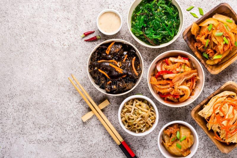 Alimento marinato coreano assortito e bastoncini su fondo grigio fotografia stock libera da diritti