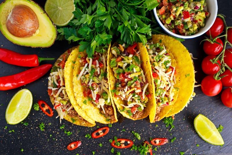 Alimento messicano - le coperture deliziose del taco con carne tritata e la casa hanno prodotto la salsa immagini stock