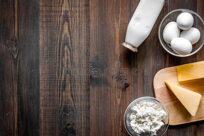 Alimento natural Leite, casa de campo, queijo, ovos no copyspace de madeira escuro da opinião superior do fundo foto de stock