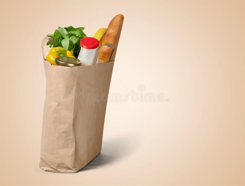 Alimento no saco de mantimento marrom isolado sobre o branco imagens de stock