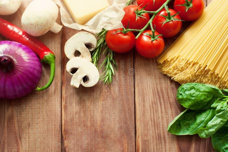 Alimento o fondo italiano degli ingredienti con gli ortaggi freschi, la pasta, il parmigiano del formaggio e le spezie Vista supe fotografie stock libere da diritti
