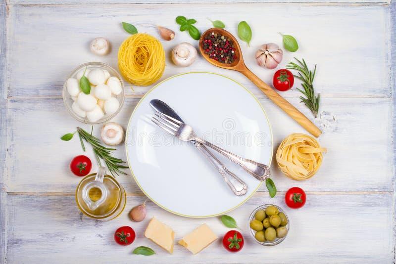 Alimento o ingredienti italiani con gli ortaggi freschi, la pasta, la mozzarella del formaggio ed il parmigiano, spezie Priorità  fotografie stock