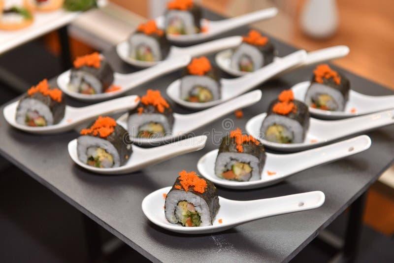 Alimento: O japonês rolou a fatia e o lugar do sushi na colher fotografia de stock