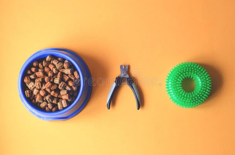 Alimento para cães em uma placa com tesouras da garra e um brinquedo foto de stock royalty free