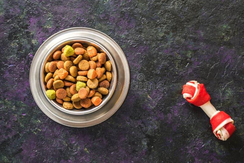 Alimento para cães na bacia metálica em escuro preto - fundo azul imagem de stock