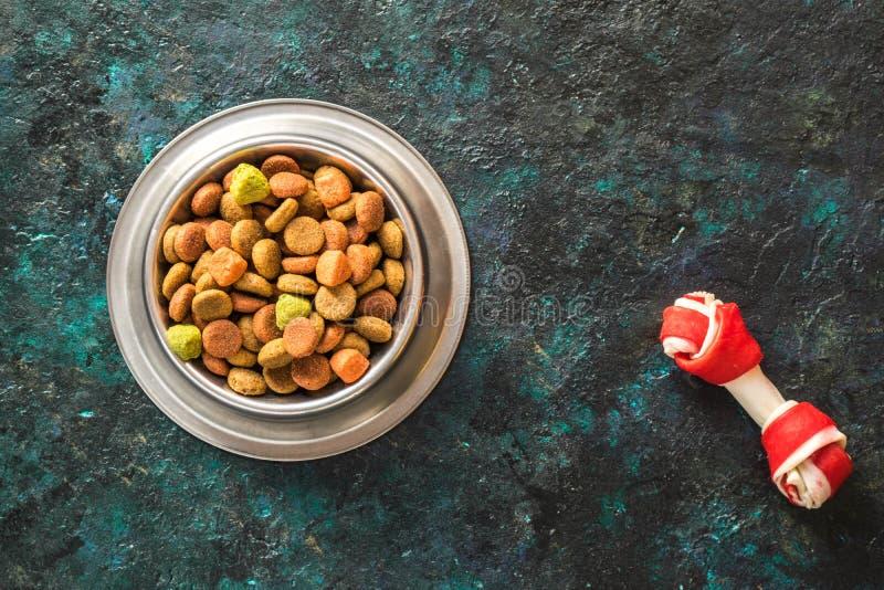 Alimento para cães na bacia metálica em escuro preto - fundo azul foto de stock royalty free