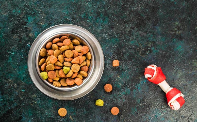 Alimento para cães na bacia metálica em escuro preto - fundo azul foto de stock