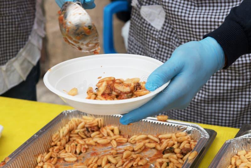 Alimento para que os pobres alimentem os hungries, conceito da doação do alimento, distribuição da massa italiana aos needies foto de stock royalty free