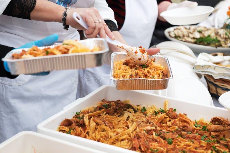 Alimento para que os pobres alimentem os hungries, conceito da doação do alimento, distribuição da massa italiana aos needies fotos de stock