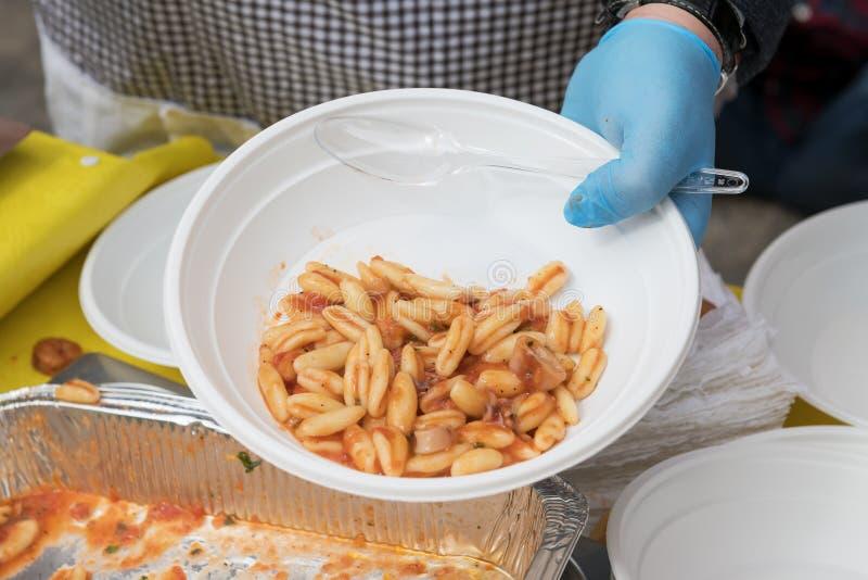 Alimento para que os pobres alimentem os hungries, conceito da doação do alimento, distribuição da massa italiana aos needies foto de stock