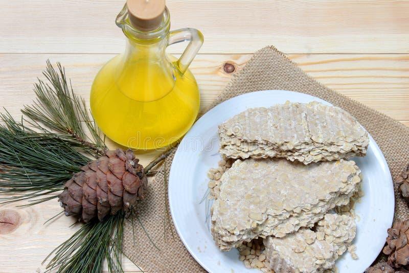 Alimento para vegetarianos O óleo do cedro em uma garrafa de vidro com o bolo de óleo do cedro na placa fotos de stock