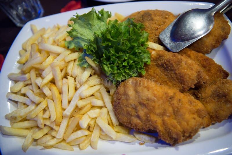 Alimento Patatas fritas y carne o pescados empanados con las hojas frescas verdes de la ensalada Tiempo de cena Almuerzo en resta imagen de archivo