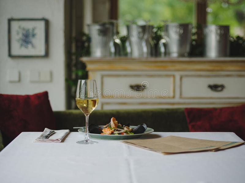 Alimento perfettamente servito ad un fondo vago del ristorante Pianta di frutti di mare cucinati e di un vetro di champagne Copi  fotografia stock
