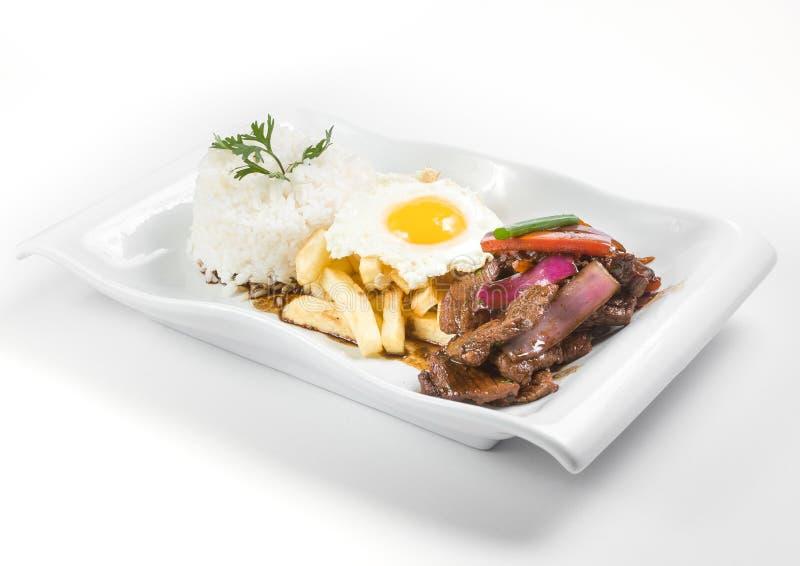 Alimento peruano: saltado do lomo com arroz e um ovo frito fotografia de stock royalty free