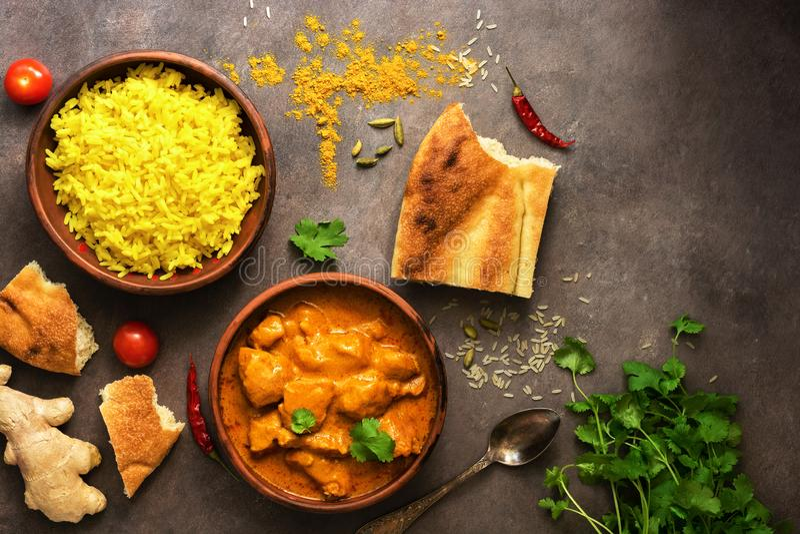 Alimento picante da carne do caril do masala do tikka da galinha, arroz e pão naan em um fundo rústico marrom Prato indiano e BRI fotografia de stock royalty free