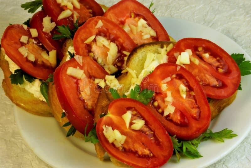 Alimento, pomodori con formaggio, aglio ed erbe fotografia stock libera da diritti