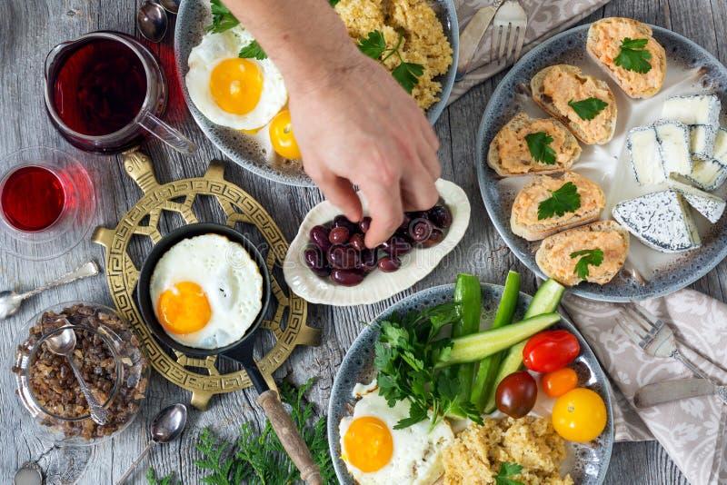 Alimento, prima colazione sana, porridge, uova, verdure, panini con il caviale fotografia stock