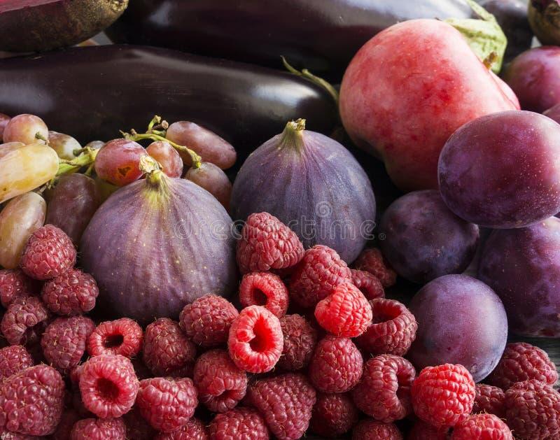 Alimento roxo Fundo das bagas, frutas e legumes Figos, ameixas, framboesas, maçãs, beringela e uvas frescos foto de stock royalty free