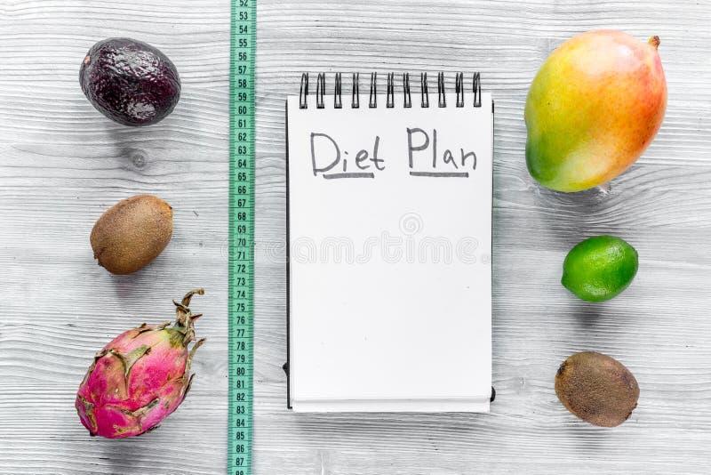 Alimento saboroso para o emagrecimento Caderno para o plano da dieta e frutos na zombaria de madeira cinzenta da opinião de tampo imagens de stock