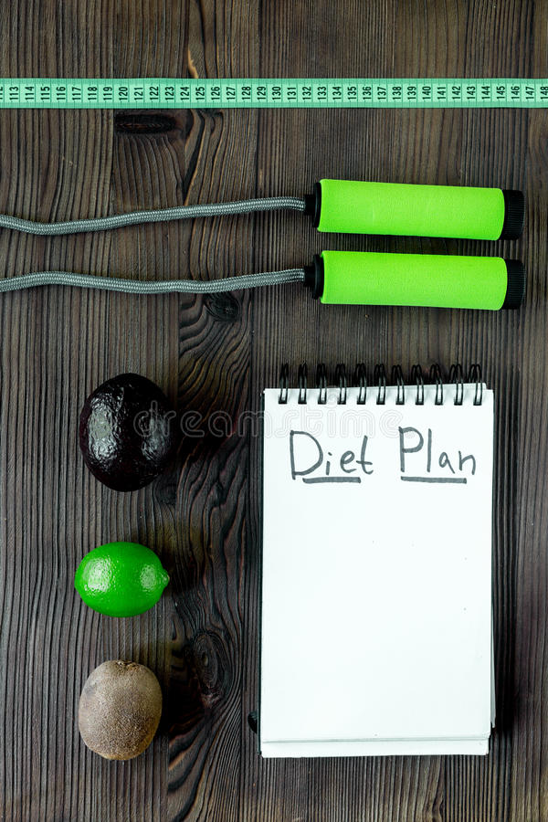 Alimento saboroso para o emagrecimento Caderno para o plano da dieta, os frutos e a fita de medição na zombaria de madeira da opi fotos de stock royalty free