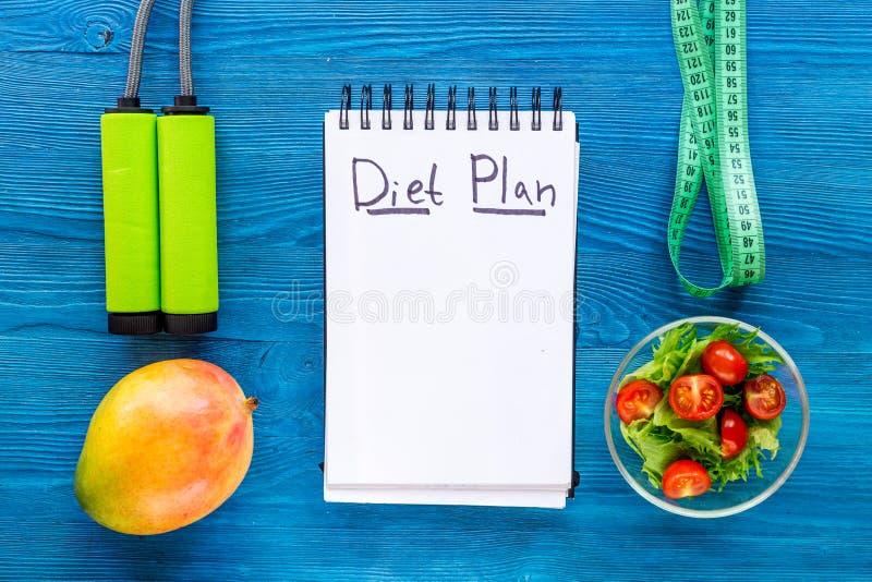 Alimento saboroso para o emagrecimento Caderno para o plano da dieta, a salada, os frutos e a fita de medição na zombaria azul da imagens de stock royalty free
