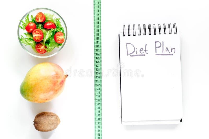 Alimento saboroso para o emagrecimento Caderno para o plano da dieta, a salada, os frutos e a fita de medição na zombaria branca  imagens de stock royalty free