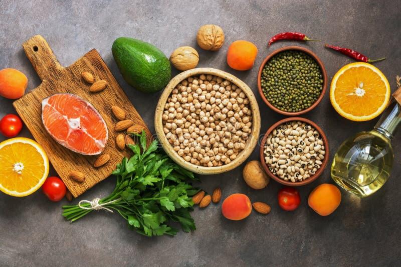 Alimento, salmone, legumi, frutta, verdure, olio d'oliva e dadi equilibrati sani, fondo rustico scuro Vista sopraelevata, disposi fotografia stock