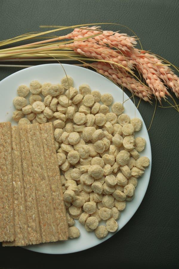 Alimento sano, alimento alternativo, pane asciutto della crusca e una spighetta del luppolo su un piatto bianco fotografia stock libera da diritti