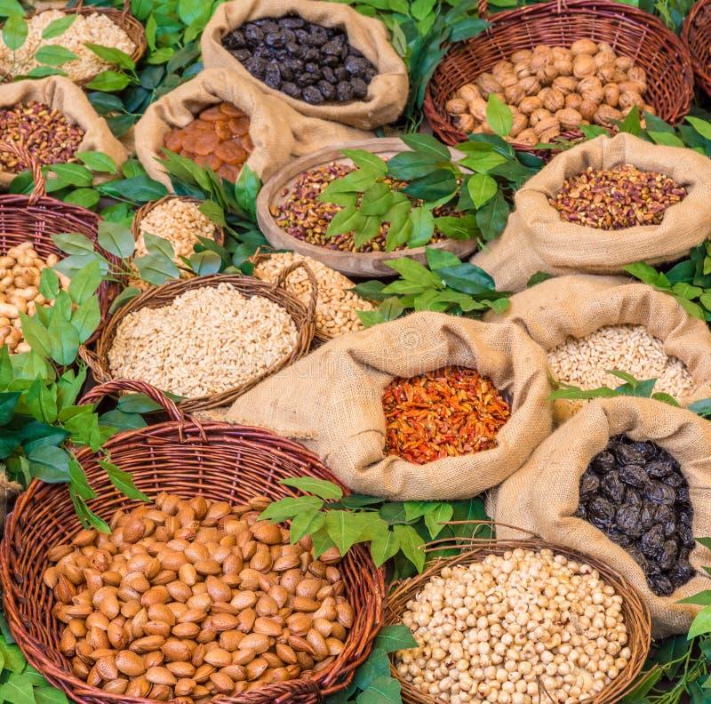 Alimento sano: assortimento di frutta secca in contenitori di legno d'annata Decorazione con alloro immagini stock