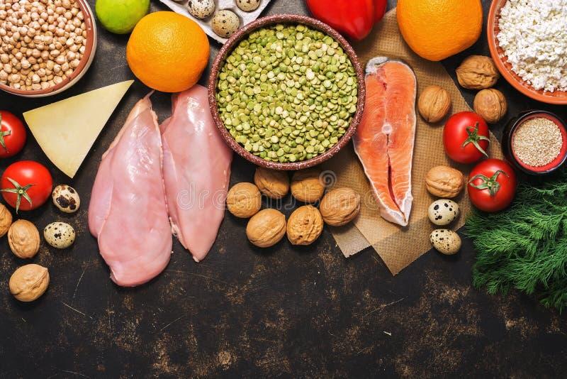 Alimento sano assortito su un fondo scuro Verdure, frutti, pesce, pollo, prodotti lattier-caseario, uova, dadi Vista superiore, s fotografia stock