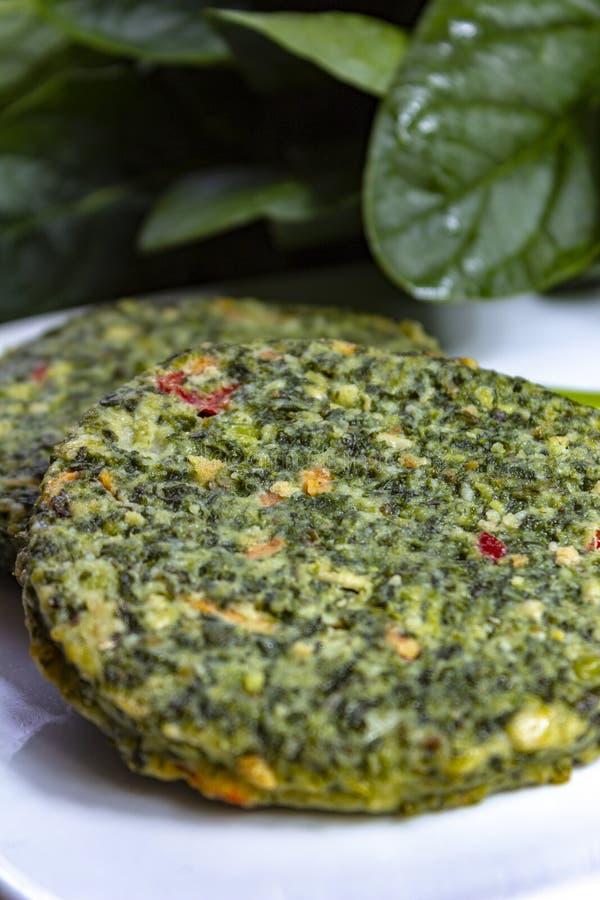 Alimento sano del vegano o del vegetariano, hamburger verdi crudi degli spinaci, ingrediente per gli hamburger immagine stock