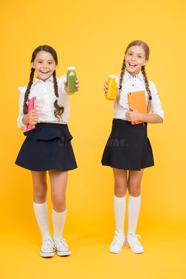 Alimento sano diario y lechería Tiempo del almuerzo pequeñas muchachas con el libro lea y escriba las muchachas felices estudian  fotos de archivo