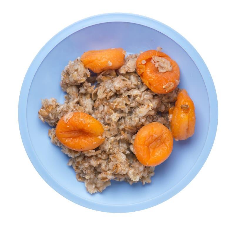 Alimento sano fiocchi del rzhanye con le albicocche secche su un piatto fiocchi piovosi isolati su fondo bianco Prima colazione d fotografie stock