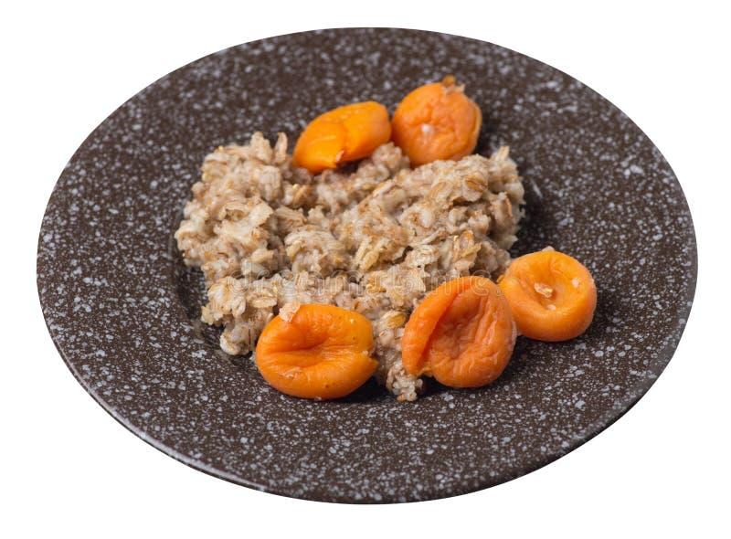 Alimento sano fiocchi del rzhanye con le albicocche secche su un piatto fiocchi piovosi isolati su fondo bianco Prima colazione d immagini stock