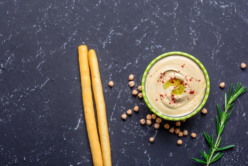 Alimento sano Fonti di proteine di verdure Ciotola di hummus, sulla tavola di pietra nera, ceci Copi la vista superiore dello spa immagine stock libera da diritti