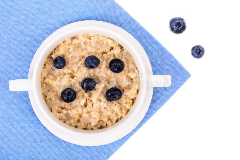 Alimento sano Gachas de avena de la harina de avena con los arándanos en servilleta azul imagen de archivo libre de regalías
