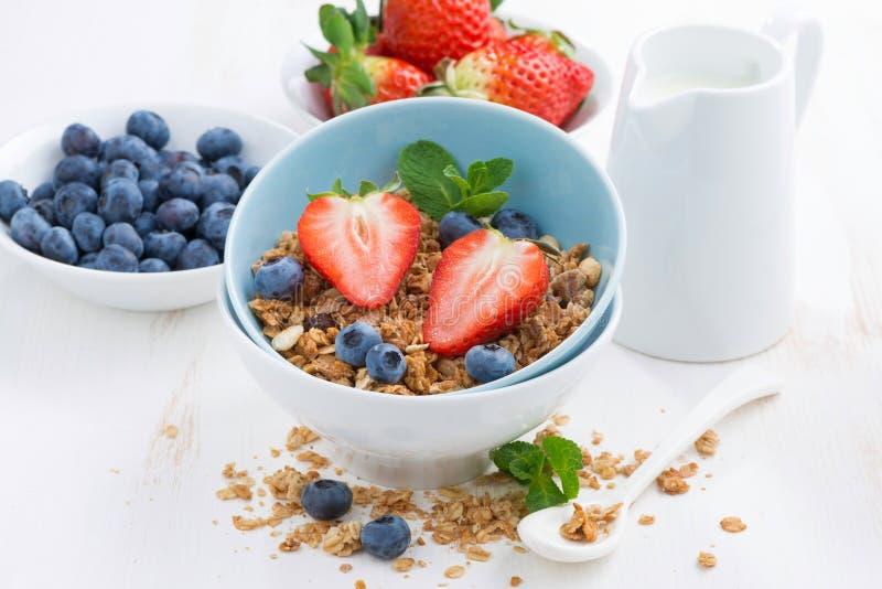 Alimento sano - granola, bacche fresche e latte sulla tavola bianca immagini stock
