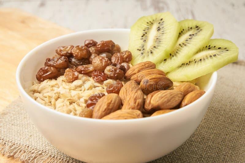 Alimento sano Harina de avena con las pasas y las almendras del kiwi imagenes de archivo