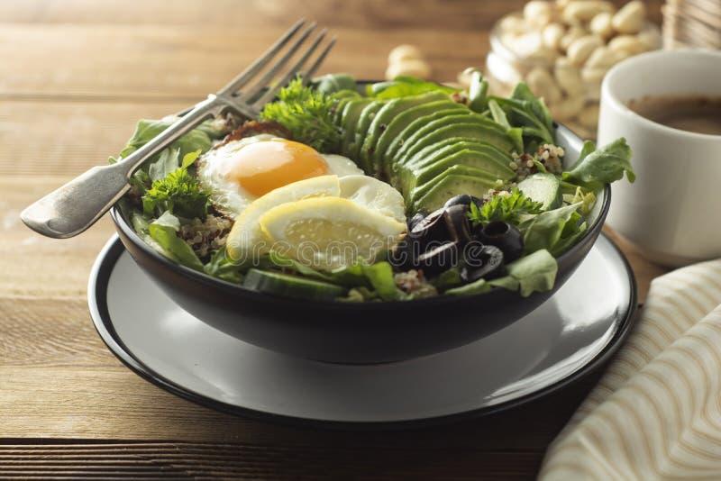 Alimento sano Huevos, quinoa, aguacate, ensalada verde, aceitunas negras Vector de madera la dieta, pierde el peso imagenes de archivo