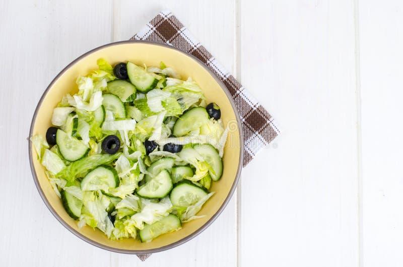 Alimento sano Insalata vegetariana dall'iceberg, dal cetriolo fresco e dalle olive nere fotografia stock