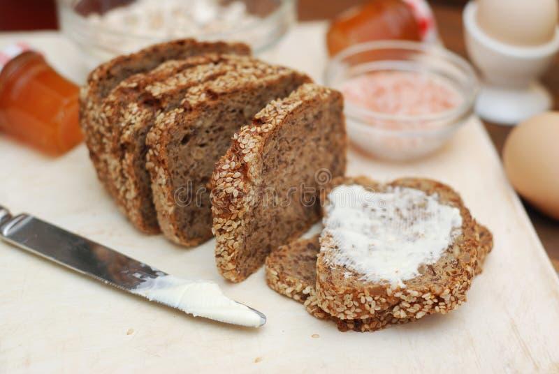 Alimento sano Intero pane rustico del grano con i semi ed il burro Concetto di dieta e sano Isolato Priorità bassa di legno immagine stock