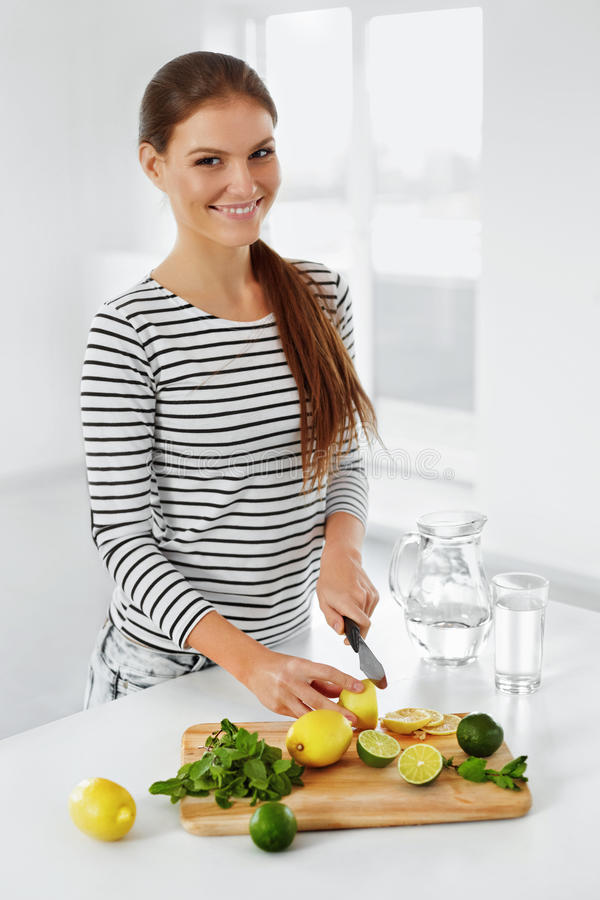 Alimento sano Limoni e limette di taglio della donna Stile di vita sano fotografia stock libera da diritti