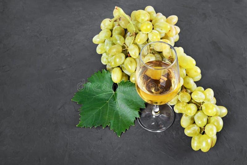 Alimento sano Manojo de opinión del primer de uva con el vidrio de vino blanco fotos de archivo