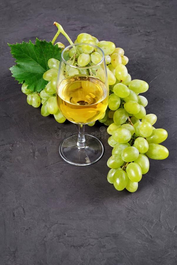 Alimento sano Manojo de opinión del primer de uva con el vidrio de vino blanco imagen de archivo libre de regalías