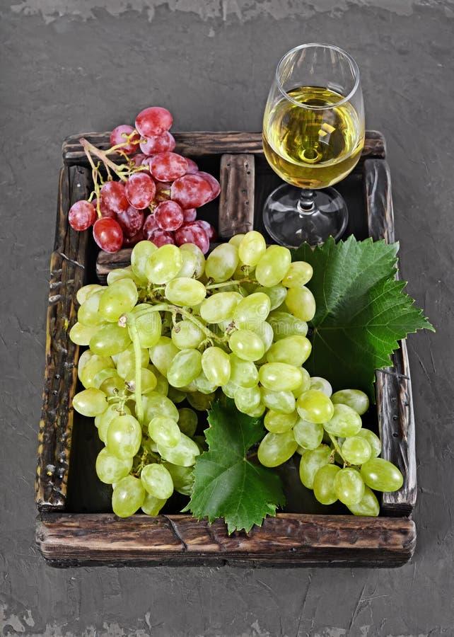 Alimento sano Manojo de opinión del primer de uva con el vidrio de vino en caja de madera del vintage imágenes de archivo libres de regalías