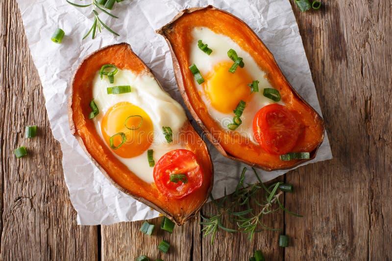 Alimento sano: patata dolce al forno con la fine del pomodoro e dell'uovo fritto immagini stock