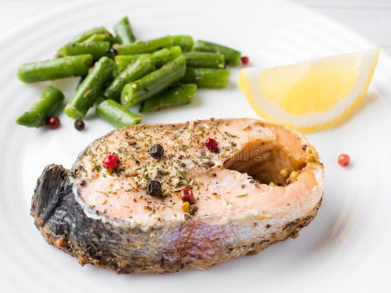 Alimento sano Pescados rojos cocidos, habas rosadas de los salmones, de color salmón y verdes con una rebanada de limón en una pl imagen de archivo